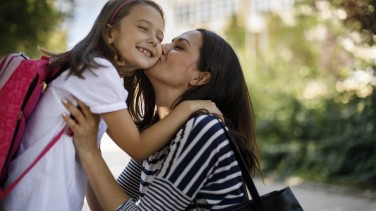 Mutter verabschiedet Kind zur Schule