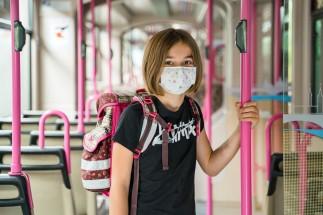 Schülerin in Straßenbahn mit Maske